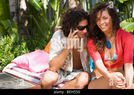 Portrait of a young woman sitting with a young man and smiling - Stock Image
