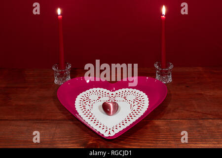 Pink heart shapped plate with dollie and gemstone, two red candles in crystal holoders on wooden table. - Stock Image