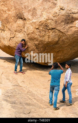 Vertical view of tourists pretending to hold up Krishna's Butterball at Mahabalipuram, India. - Stock Image