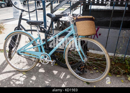 Woman's bicycle with basket locked to fence and another bicycle in Kensington Market in downtown Toronto Ontario - Stock Image