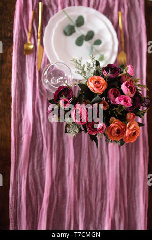 Wooden table is covered with a color runner tablecloth with a white plate and bouquet of roses - Stock Image