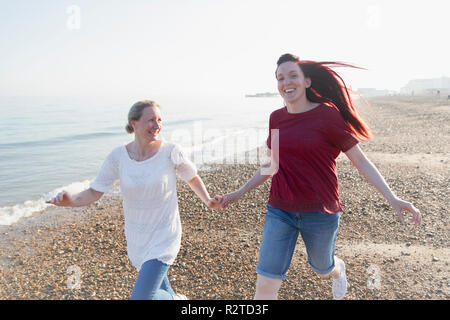 Playful lesbian couple running on sunny beach - Stock Image