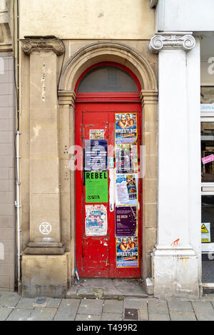 Red door with advertising posters and flyers attached - Stock Image