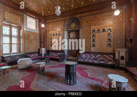 Manial Palace of Prince Mohammed Ali. Guests Hall with wooden ornate ceiling, wooden ornate door, lanterns, colorful ornate couches, tea tables - Stock Image