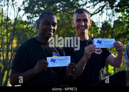 U.S. Air Force Chief Master Sgt. Christopher McKinney, 20th Fighter Wing (FW) command chief, left, and Col. Daniel Lasica, 20th FW commander, right, hold up their Air Force Assistance Fund (AFAF) donation slips during the Weasel Walk at Shaw Air Force Base, S.C., April 10, 2017. To kick off Shaw's AFAF campaign 20th FW leadership signed donation slips toward the base's goal of $95,153. (U.S. Air Force photo by Airman 1st Class Destinee Sweeney) - Stock Image
