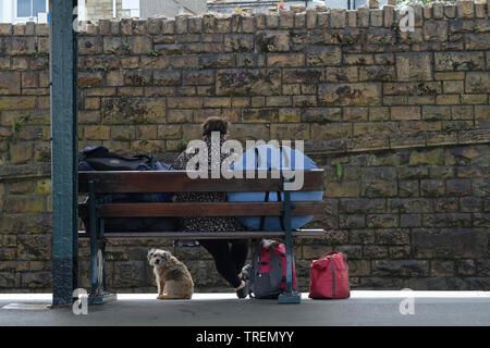 A Woman and her dog waiting​ on a train platform. - Stock Image