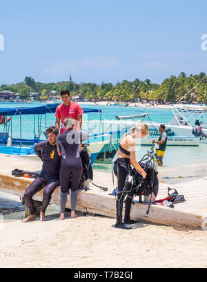 SCUBA enthusiasts prepare to dive on the Mesoamerican Barrier Reef off West Bay Roatan Honduras. - Stock Image