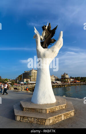 KUSADASI, TURKEY - MAY 23, 2015: The hand of peace sculpture with doves on the waterfront in Kusadasi, Turkey. - Stock Image
