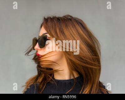Pretty teen girl blonde hair portrait blowing wind with sunglasses looking away aside - Stock Image