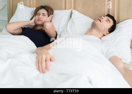 Annoyed Asian wife blocking her ears from noise of husband snoring in bedroom at home. Young couple have problem with man's snoring. - Stock Image
