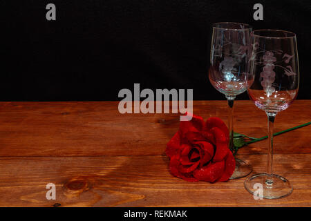 Beautiful etched wine glasses with a single red rose on wooden table and dark background. Valentines, Mothers Day, Easter, Christmas, Wedding Concepts - Stock Image