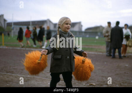 1960s, historical, USA, little girl holding a pair of colourful, orange 'pom-poms' outside on the track of a sports ground. Pom-Poms are used by 'cheerleaders', groups of girls who support or 'cheer' for their team, most commonly in American football team to entertain the spectators and to add sparkle to the event. - Stock Image