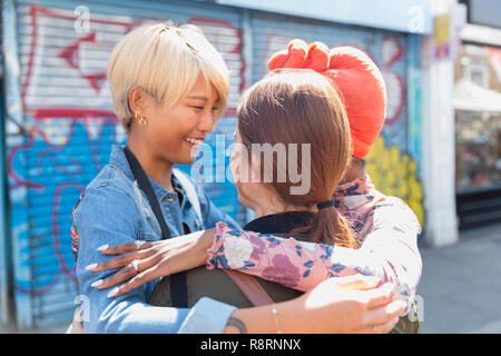 Happy young women friends hugging on urban sidewalk - Stock Image