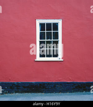 Single white framed window set against a red painted house brickwall - Stock Image