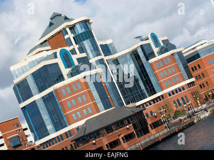A photo of the Victoria Building at Salford Quays taken from across the water at a tilted angle. - Stock Image