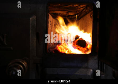 Fire burning in an old wood stove. - Stock Image
