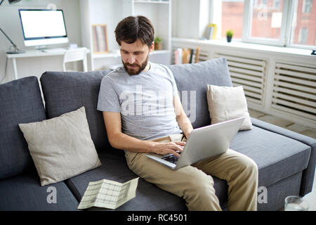 Young accountant looking at financial data on paper wnd entering it in laptop while working on sofa in home office - Stock Image