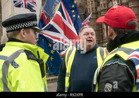 London, UK. 19th December 2018. Extreme right Brexiteers insult police.  A small group of extreme right-wing pro-Brexit protesters came to shout and argue with the daily SODEM (Stand of Defiance European Movement) protesters and to shout personal insults at Steven Bray who founded SODEM in September 2017. Police tried hard to keep the clashes peaceful, and warned the right-wing protesters about their language. The Brexiteers then accused the police of taking sides. Eventually they moved away to protest outside parliament. Peter Marshall/Alamy Live News - Stock Image