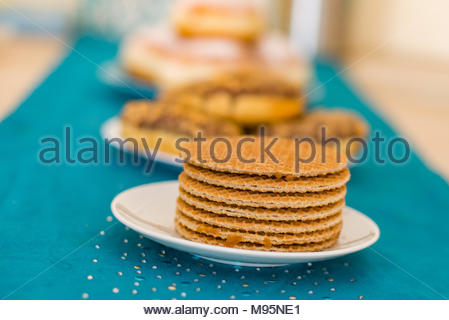 Pile of sweet Dutch stroopwafels on a white plate in soft focus - Stock Image