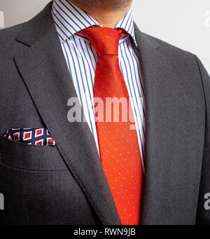Business Power, Detail closeup - jacket men's, shirt with a orange tie and pocket square - Stock Image