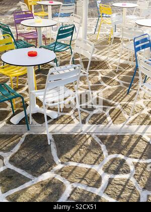 Colourful chairs and tables at sunset - Stock Image