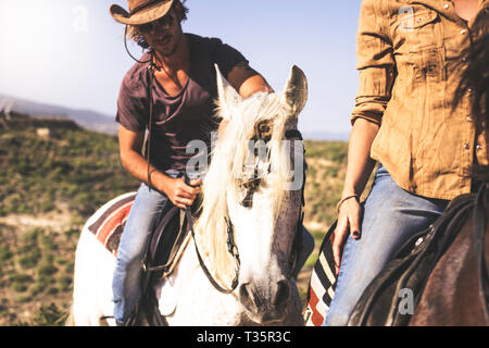 Couple of young alternative millennial man and woman riding horse in the nature - outdoor leisure activity for beautiful people with animals - Stock Image