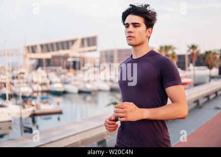 Young athletic man running at park during skyscrapers background - Stock Image