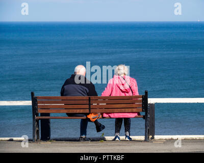 Middle aged white couple on a bench overlooking the sea at Saltburn North Yorkshire on a fine sunny autumn day - Stock Image