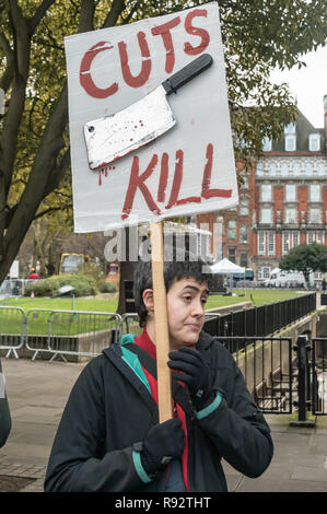 London, UK. 19th Dec, 2018. A woman holds the 'Cuts Kill' placard at the protest by Disability group DPAC to support the parliamentary debate due later in the day on the cumulative impact of the cuts on the lives of disabled people. They say the government cuts and changes in benefits, along with inappropriate benefit sanctions, have had a disproportionate effect on disabled people, resulting in great hardship, denying people their rights and many deaths. Credit: Peter Marshall/Alamy Live News - Stock Image