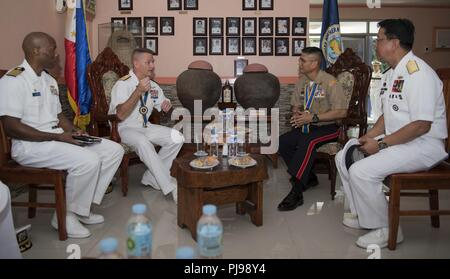 SAN FERNANDO CITY, Philippines (July 9, 2018) Rear Adm. Joey Tynch, Commander, Task Force 73 (center-left) and Capt. Lex Walker, Commodore, Destroyer Squadron 7 (left), participate in an office call with Philippine Lt. Gen. Emmanuel Salamat, Commander, Northern Luzon Command (center-right), and Philippine Commodore Nichols Driz, Commander, Naval Forces Northern Luzon, during Maritime Training Activity (MTA) Sama Sama 2018. The week-long engagement focuses on the full spectrum of naval capabilities and is designed to strengthen the close partnership between both navies while cooperatively ensur - Stock Image