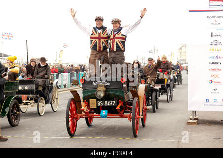 Mr Mark Farrall and Friend celebrating in their 1901 Albion, at the finish line of the 2018 London to Brighton Veteran Car Run. - Stock Image