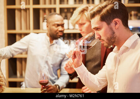 Young man with friends at a wine tasting smells at a glass of red wine - Stock Image