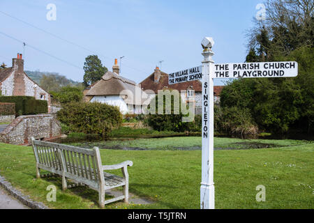 Empty bench and signpost on a country village green by pond in South Downs National Park. Singleton, Chichester, West Sussex, England, UK, Britain - Stock Image
