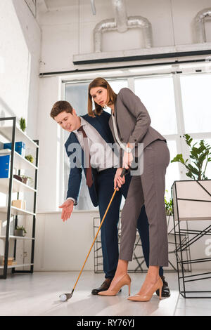 handsome businessman gesturing while looking at ball near female coworker playing mini golf in office - Stock Image