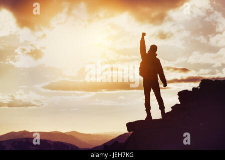Man winner mountain top silhouette - Stock Image