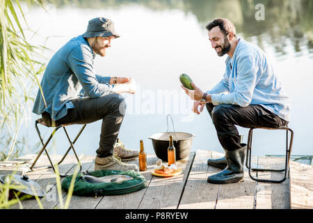 Two friends sitting together with beer and fish on the picnic while fishing near the lake - Stock Image