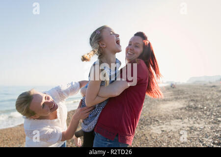 Lesbian couple and daughter laughing on sunny beach - Stock Image