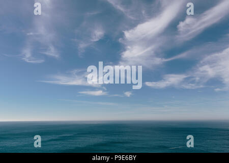 View over the ocean to the horizon, deep blue sea and light windblown wispy clouds in the sky. - Stock Image