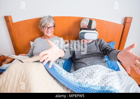Couple of senior people married rest in bed, reading or making new experience with virtual reality. Happy retired caucasian man and woman - Stock Image