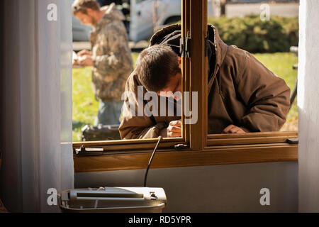 A Causian workman repairs and rebuilds a wooden window sill from outdoors on a winter day. USA. - Stock Image
