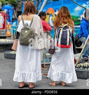 Two girls dressed in white full length dresses. Cool summer clothing - Stock Image