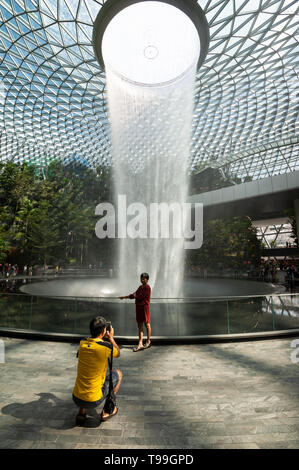 18.04.2019, Singapore, , Singapore - A man photographs his wife in front of the waterfall in the new Jewel Terminal at Changi International Airport. T - Stock Image
