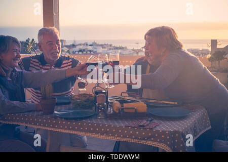 Active senior elderly people concept with group of mature friends having dinner together at home in the terrace with city and ocean view - celebration - Stock Image