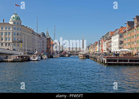 View through Nyhavn canal with vintage ships and colourful houses towards Kongens Nytorv in Copenhagen. Crowded bars and restaurants and vintage ships - Stock Image