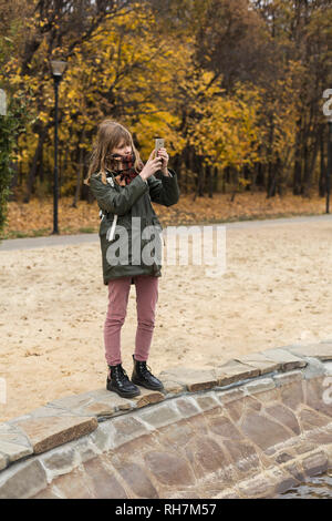 Tween girl using camera phone in autumn park - Stock Image