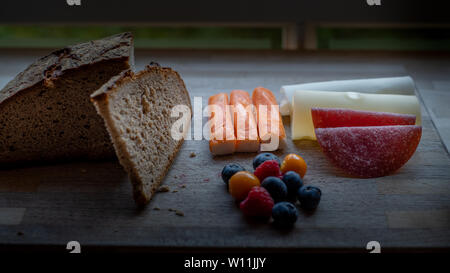 A low-carb , protein-rich meal consisting of swiss cheese, salami; berries, fake fish  and rye bread on wooden plate by a window - Stock Image