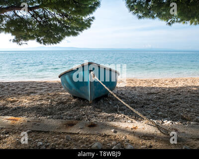 Small plastic boat on the beach under pine trees on sunny summer day - Stock Image