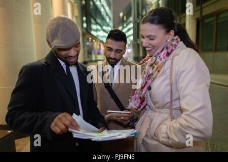 Business people reviewing paperwork on urban sidewalk at night - Stock Image
