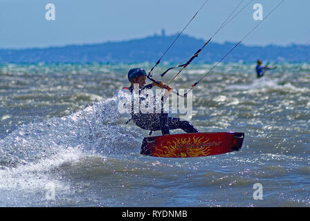 Kite boarder in flying over the waves during a windy day in french riviera - Stock Image