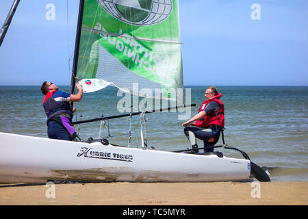 Two sailors preparing Hobie Cat, small sailing catamaran on the beach along the North Sea coast - Stock Image
